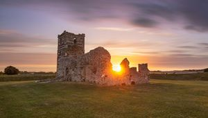 Sun setting on Knowlton Church, in Cranborne.