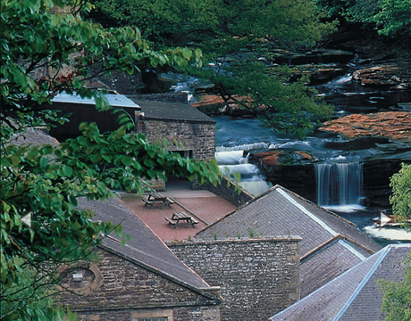 Cascading water from the pretty River Clyde provided power to the 18th-century mills of New Lanark.