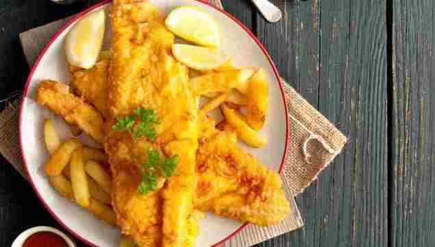Two pieces of battered fish on a plate with chips.