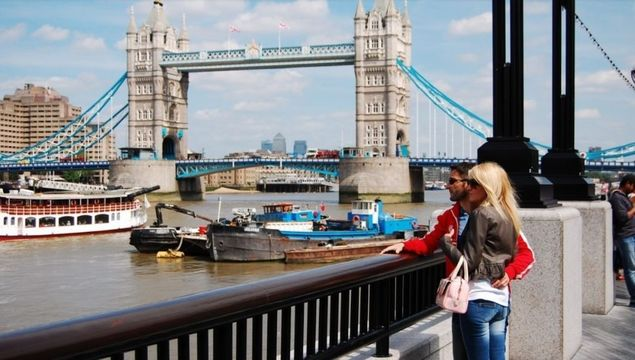 Tourists enjoying Tower Bridge and the River Thames, in London.