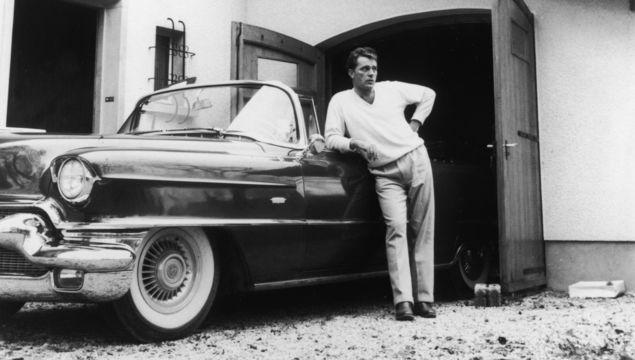 Welsh actor Richard Burton (1925 - 1984) leaning on a Cadillac convertible, circa 1955.