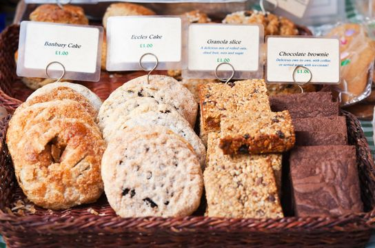 Hand made Banbury Cakes, Eccles Cakes, Granola Slices and Chocolate Brownies for sale on a stall at a UK Farmer's Market.