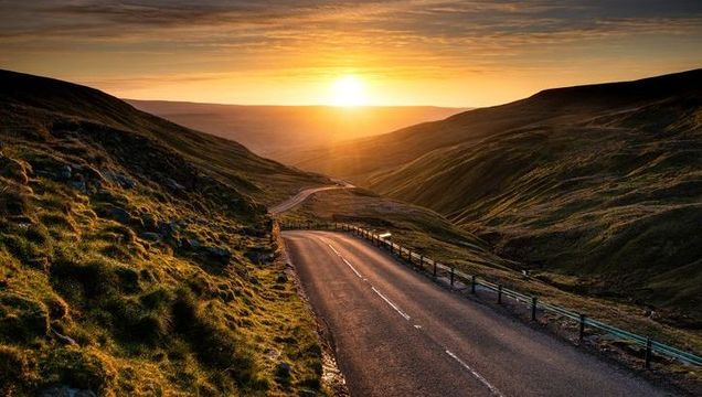 Sunrise over winding mountain road in Yorkshire dales, England.