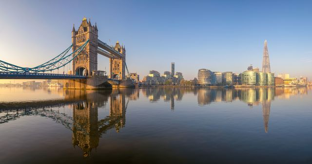 A panoramic view of the River Thames, spanning from Tower Bridge to the Shard. The still water offers a perfect reflection of the city skyline.