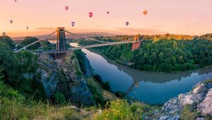 Many Hot Air Balloons drift towards Clifton Suspension Bridge in Bristol at sunrise. The bridge spans the River Avon gorge.