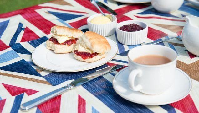A traditional English cream tea scone with jam and cream.