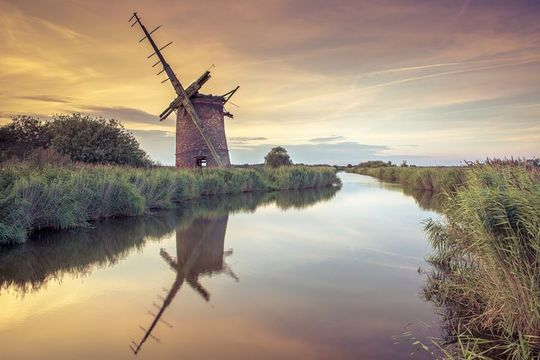 Abandoned Windmill on norfolk broads at sunset.