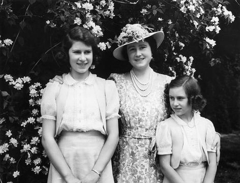 Queen Elizabeth with, on the left, her daughter Princess Elizabeth (later Queen Elizabeth II) and on the right Princess Margaret (1930 - 2002), in the garden at Windsor Castle during WW II.