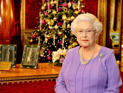 Britain\'s Queen Elizabeth II poses in the State Dining Room of Buckingham Palace after recording her Christmas Day television broadcast to the Commonwealth on December 10, 2014 in London. On the table are portraits of the Queen\'s grandfather King George V and Queen Mary along with a decorated brass tin given to all members of the British, Colonial and Indian Armed Forces for Christmas 1914 at the suggestion of their daughter Princess Mary. (Photo by John Stillwell - WPA Pool/Getty Images)