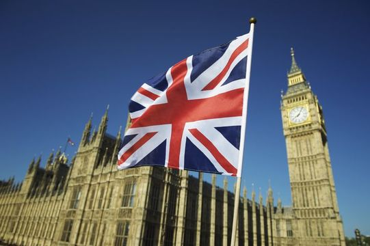 Union Jack, the United Kingdom flag flying next to Westminster and Big Ben.