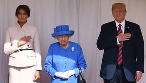 Britain\'s Queen Elizabeth II (C) stands with US President Donald Trump (R) and US First Lady Melania Trump (L) on the dias in the Quadrangle listening to a band of guardsmen play the US national anthem during a ceremonial welcome at Windsor Castle on July 13, 2018 in Windsor, England