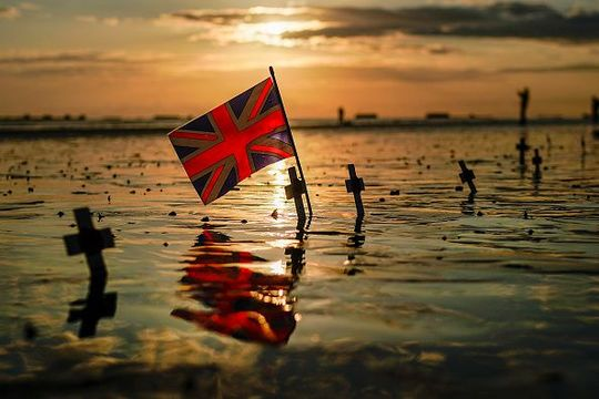 A Union Flag is planted alongside crosses on Gold Beach near the Mulberry harbour on the morning of the 75th anniversary of the D-Day landings on June 6, 2019