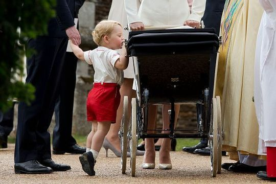 Prince George of Cambridge looks at his sister Princess Charlotte of Cambridge in her pram as he leaves the Church of St Mary Magdalene on the Sandringham Estate for her christening