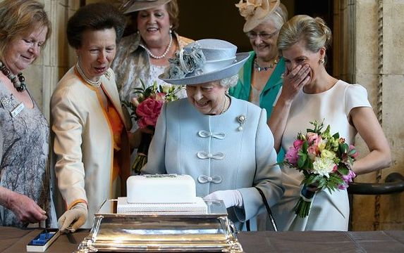 Sophie, Countess of Wessex and Princess Anne, Princess Royal look on as Queen Elizabeth II cuts a Women\'s Institute Celebrating 100 Years cake at the Centenary Annual Meeting of The National Federation Of Women\'s Institute at the Royal Albert Hall.