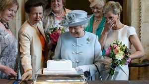 Sophie, Countess of Wessex and Princess Anne, Princess Royal look on as Queen Elizabeth II cuts a Women\'s Institute cake.