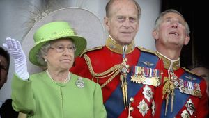 Queen Elizabeth II raises her hand during a downpour as she stands with (L-R) Prince Philip, Duke of Edinburgh and Prince Charles, Prince of Wales on the balcony of Buckingham Palace after the Trooping the Colour ceremony on June 16, 2007 in London. Each year the official birthday of Queen Elizabeth II is commemorated with a military parade and march-past of fully trained, operational troops from the Household Division