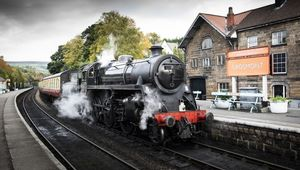 A stream train arriving at the platform of a traditional station in North Yorkshire.