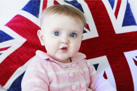 LONDON, ENGLAND - FEBRUARY 2: A wide eyed young infant looks directly at the viewer in curiosity set against the backdrop of the British flag, the Union Jack. on February 02, 2017 in London, United Kingdom.