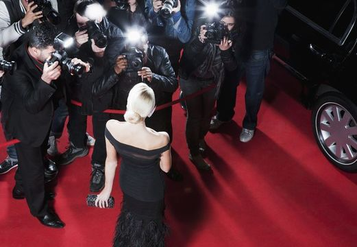 Celebrity posing for paparazzi on red carpet - stock photo