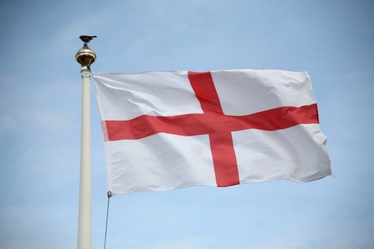 England St George flag blowing in the wind on a fine day. With a robin red breast sat on flagpole!