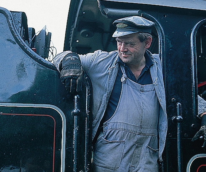 A railroad fireman greets passengers on the 'Jacobite' steam train at Fort William.