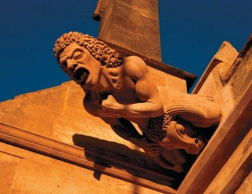 A gargoyle perched of Gloucester Cathedral.