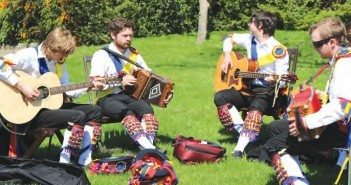 A colorful young side of Morris Dancers warm up on the grass in the New Forest.